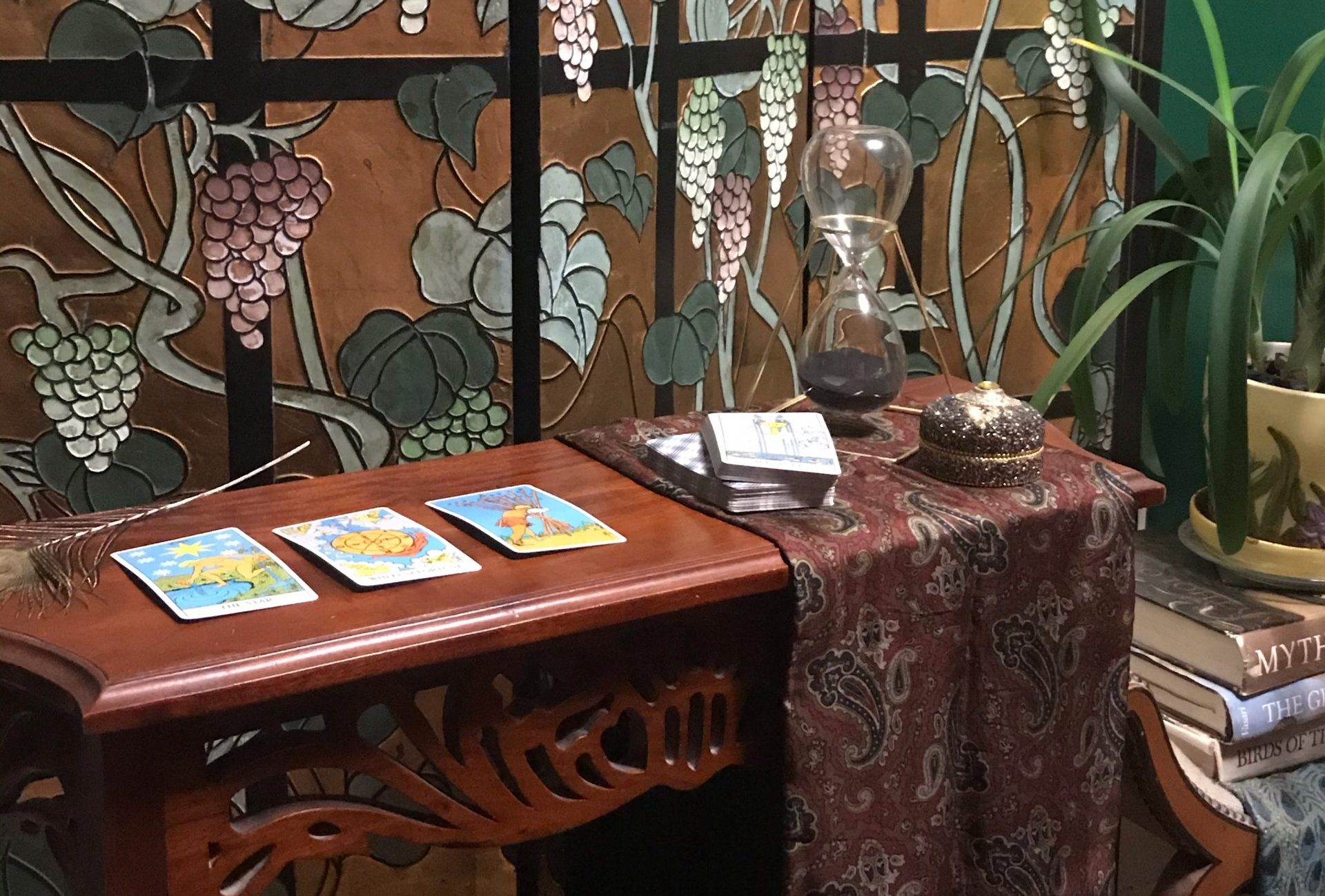 Tarot cards laid out on a table, with a room divider with grapes on it in the background.