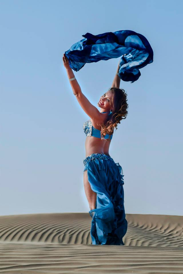 A woman doing a belly dance with a blue scarf in the sand