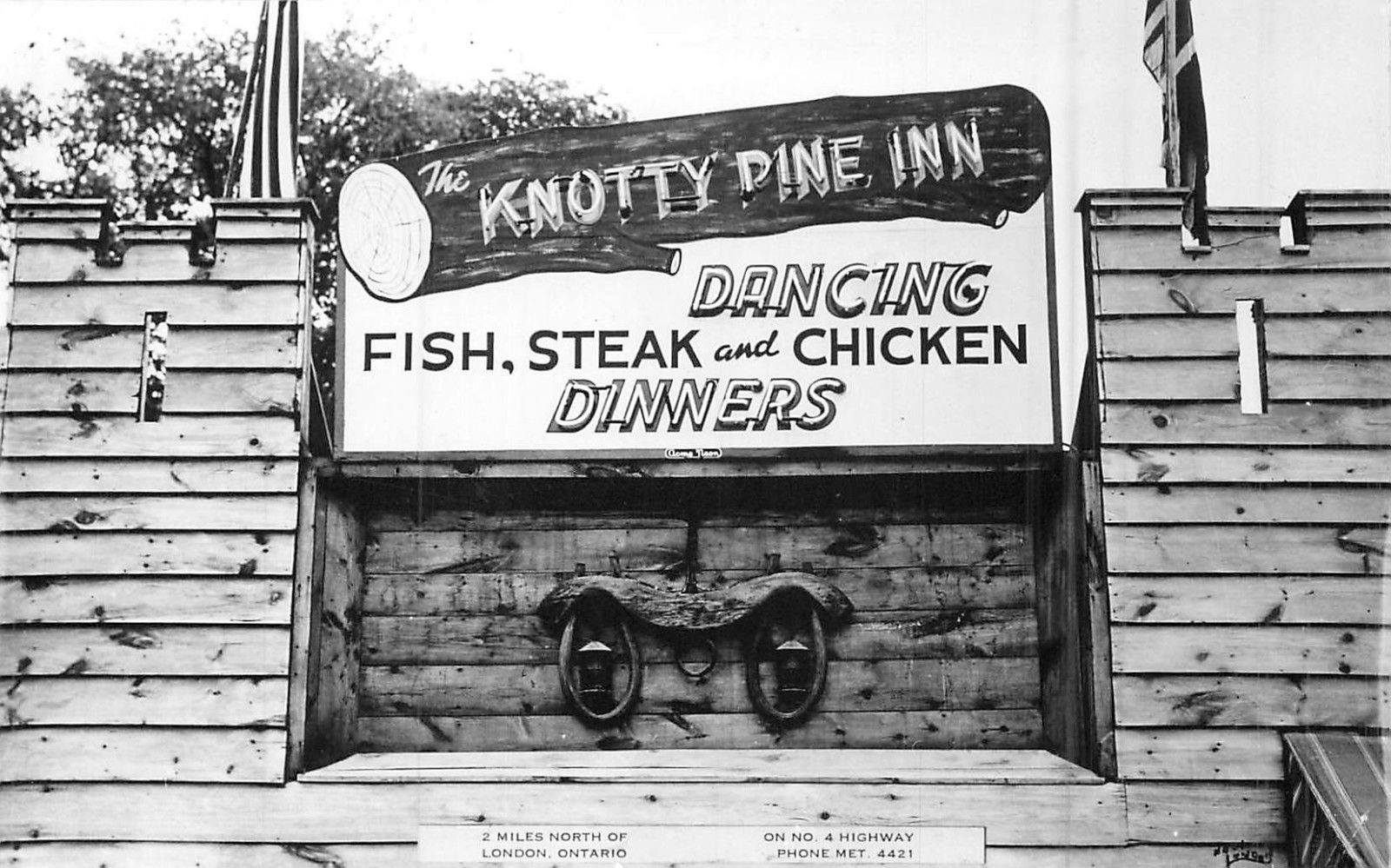 """A wooden building with a sign that says """"Knotty Pine Inn Dancing Fish, Steak, and Chicken Dinners"""""""