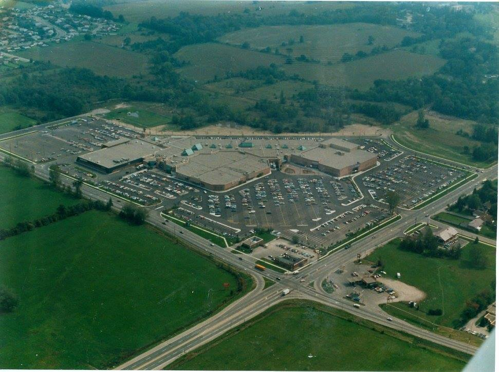 An aerial view of a shopping mall surrounded by green fields.