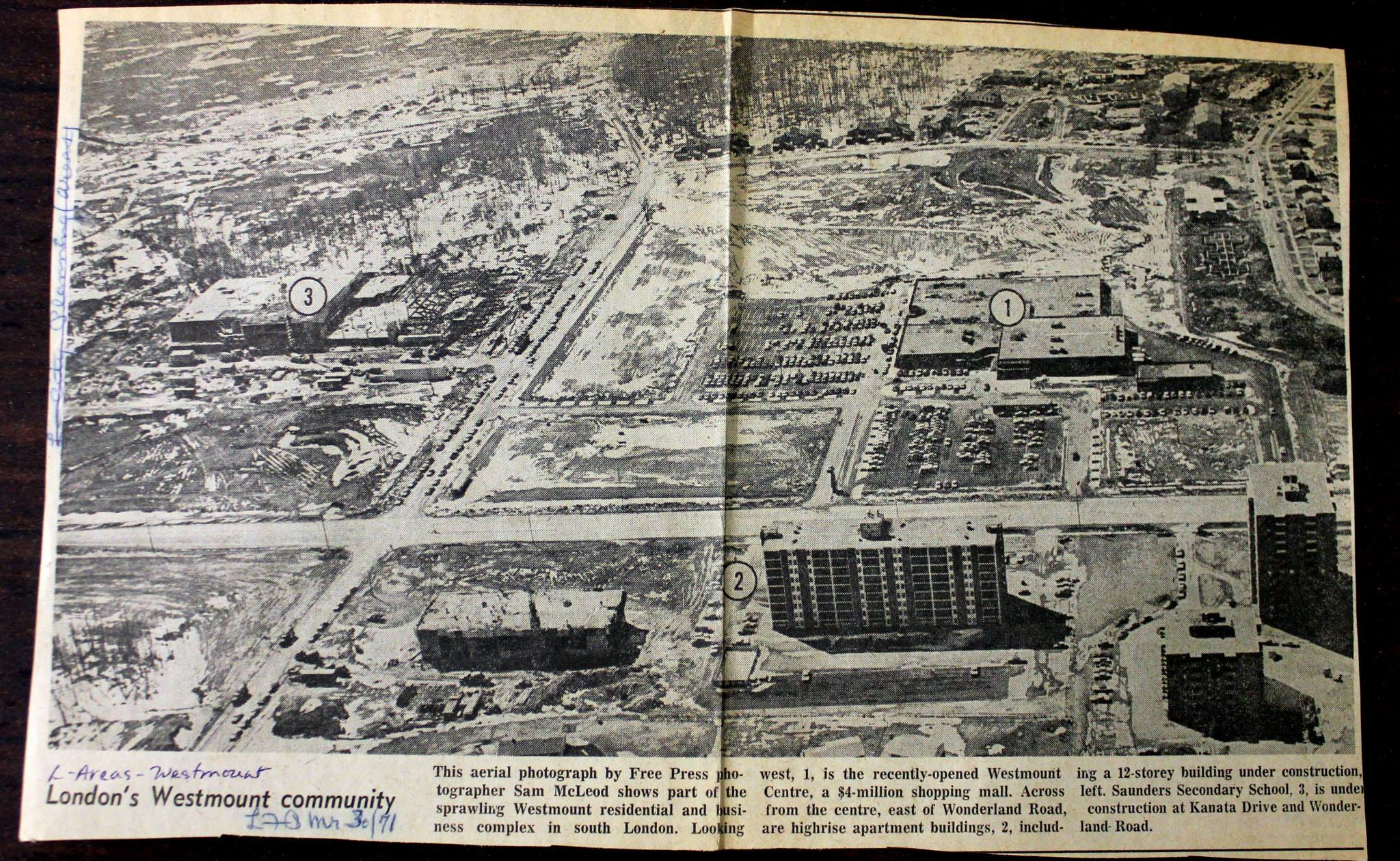 A black and white newspaper clipping with an aerial photo of Westmount, showing several high rises and an intersection.