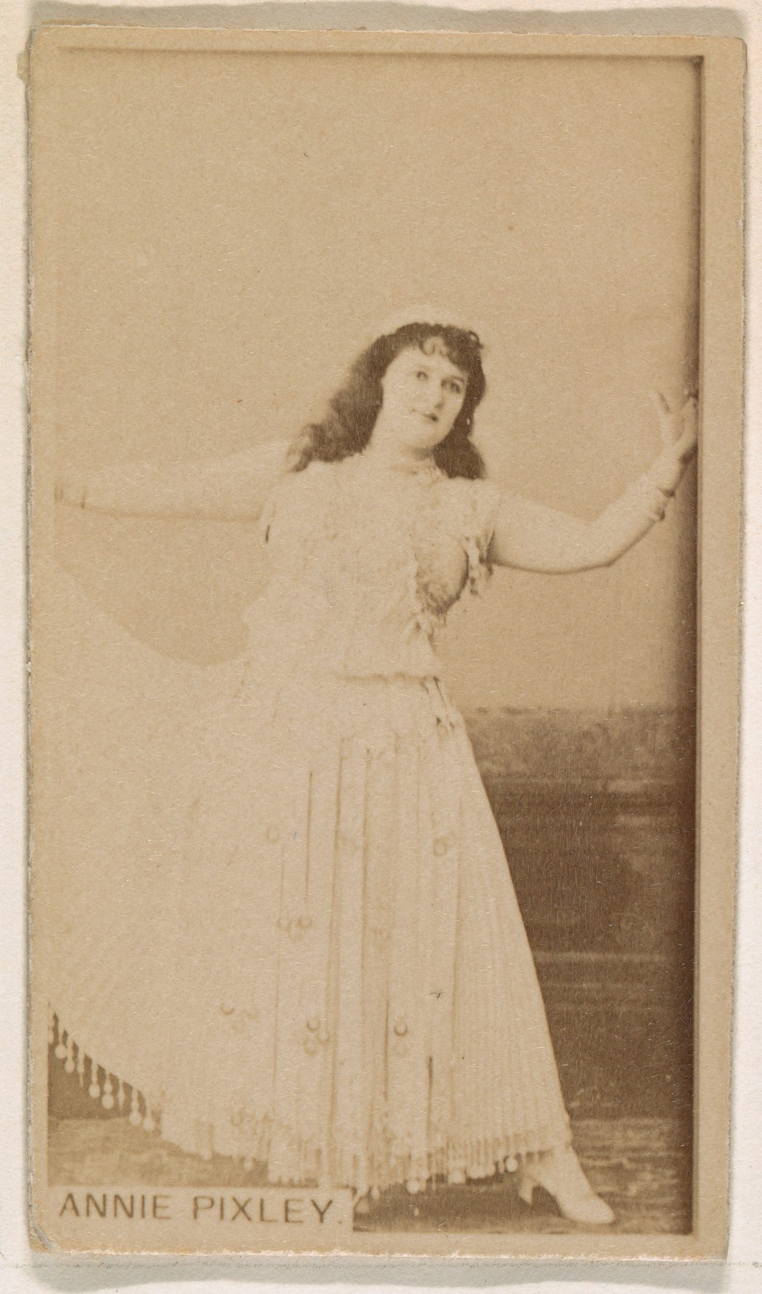a sepia tone photo of. woman wearing a white dress holding her arms out on her sides