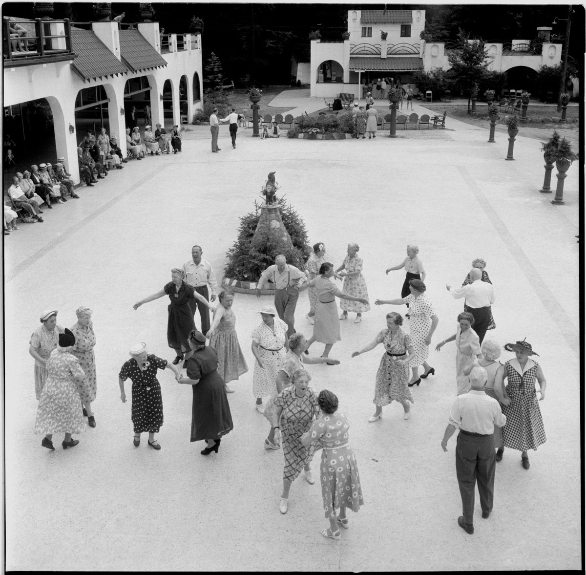 A black and white photo shows a group of 25 senior citizens dancing on an outdoor ballroom in Westmount