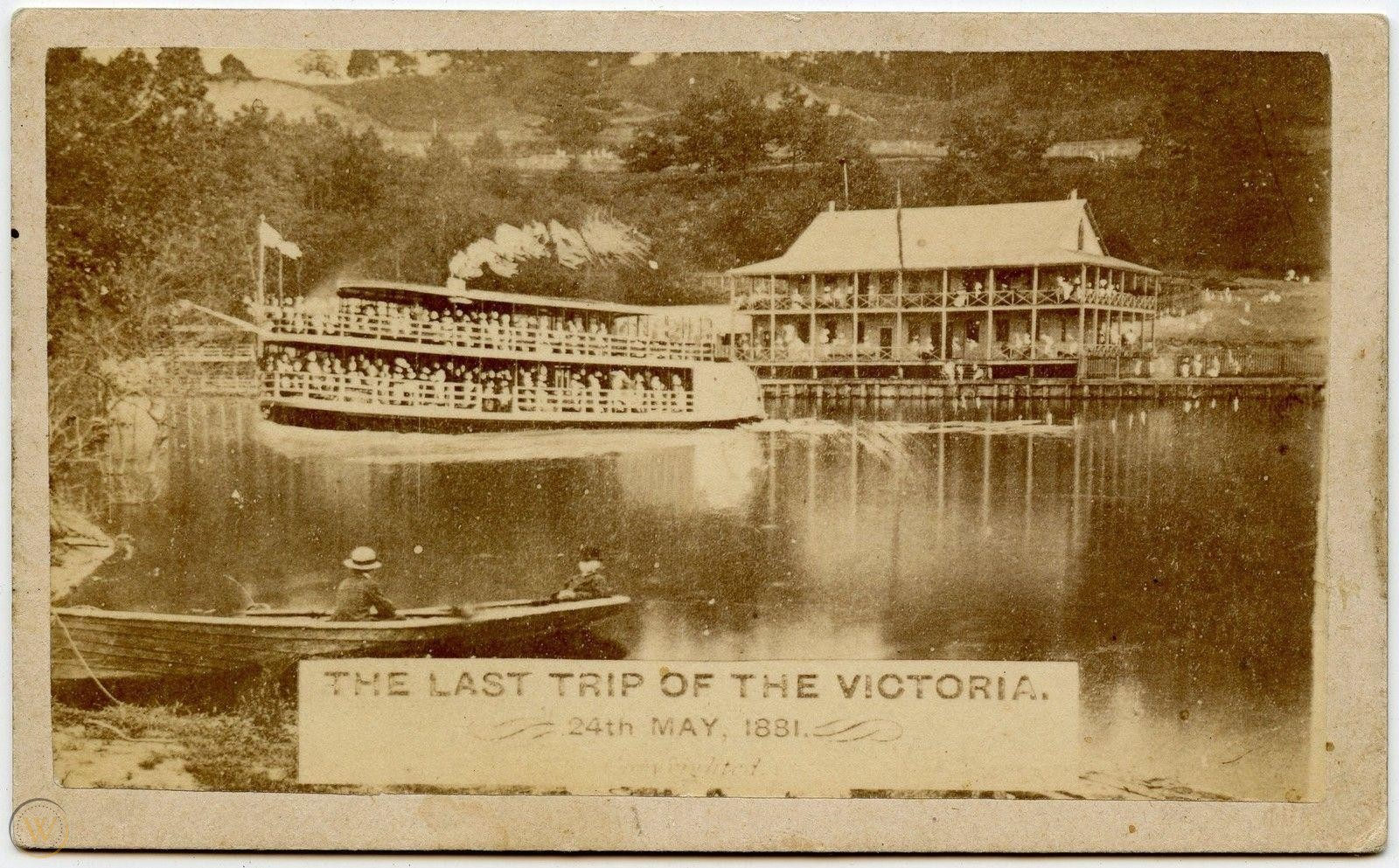 A sepia toned image of a boat full of people leaving a wharf also full of people.