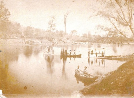 A sepia tone image of rowers headed out onto the Thames River.