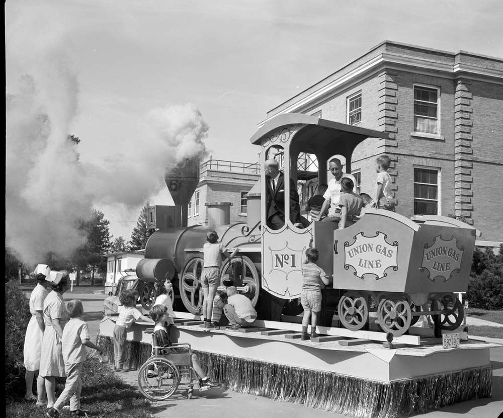 a black and white photo of children climbing a mini train with nurses standing by.
