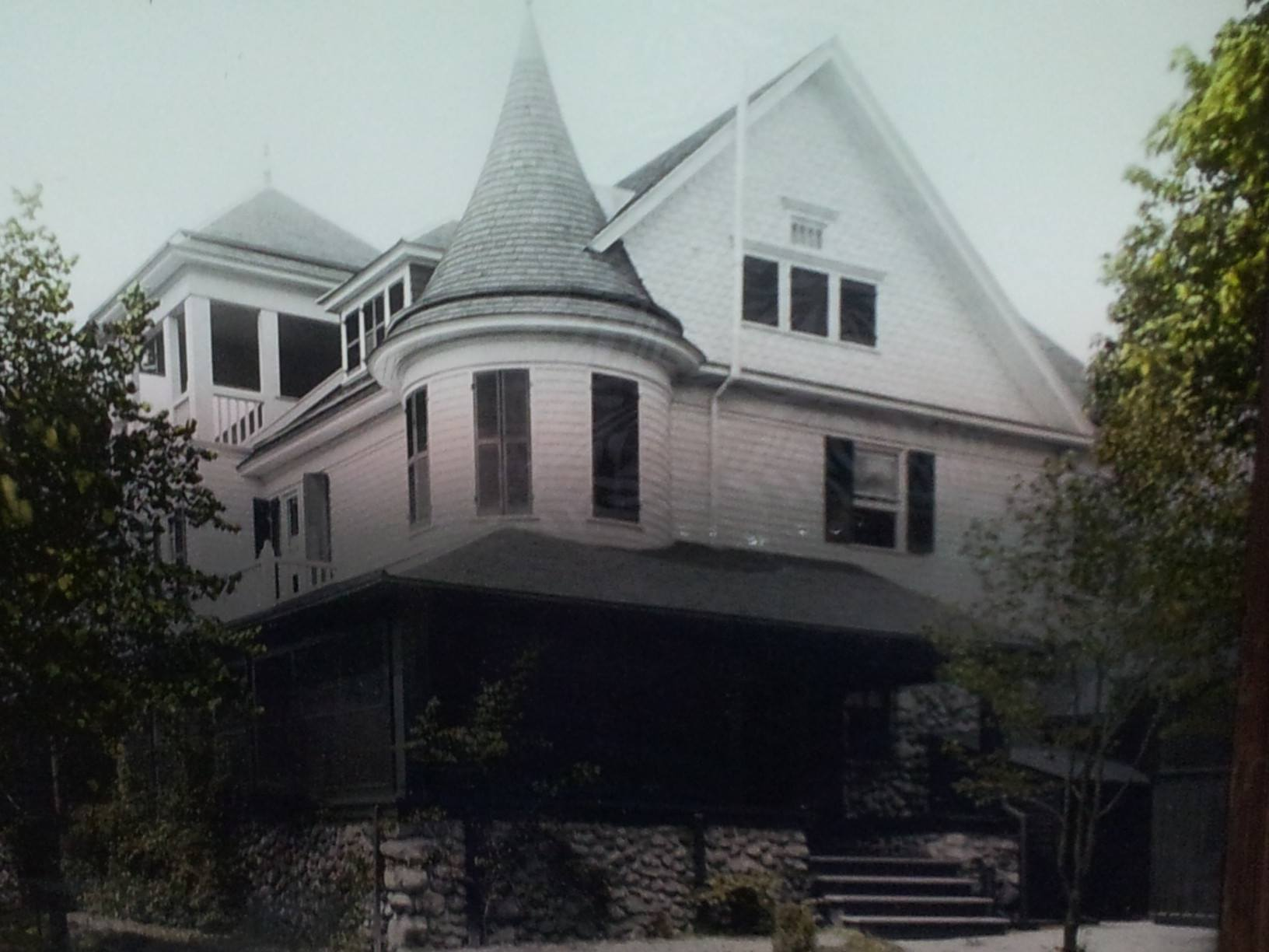 A distorted image of a large house, partially in colour, partially in black and white.