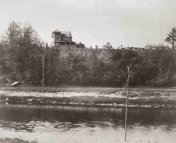 A black and white photo of Oakridge's Hazeldon Manor atop a cliff with the river in the forefront.