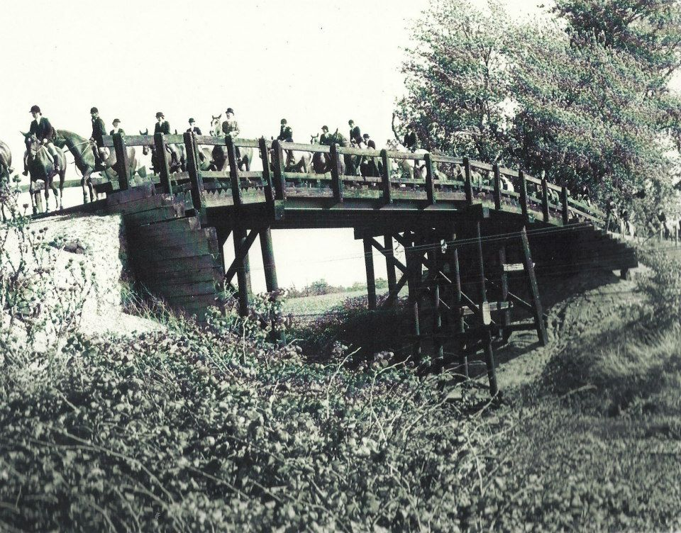 A black and white photo of a group of people on horses riding across a wooden bridge.
