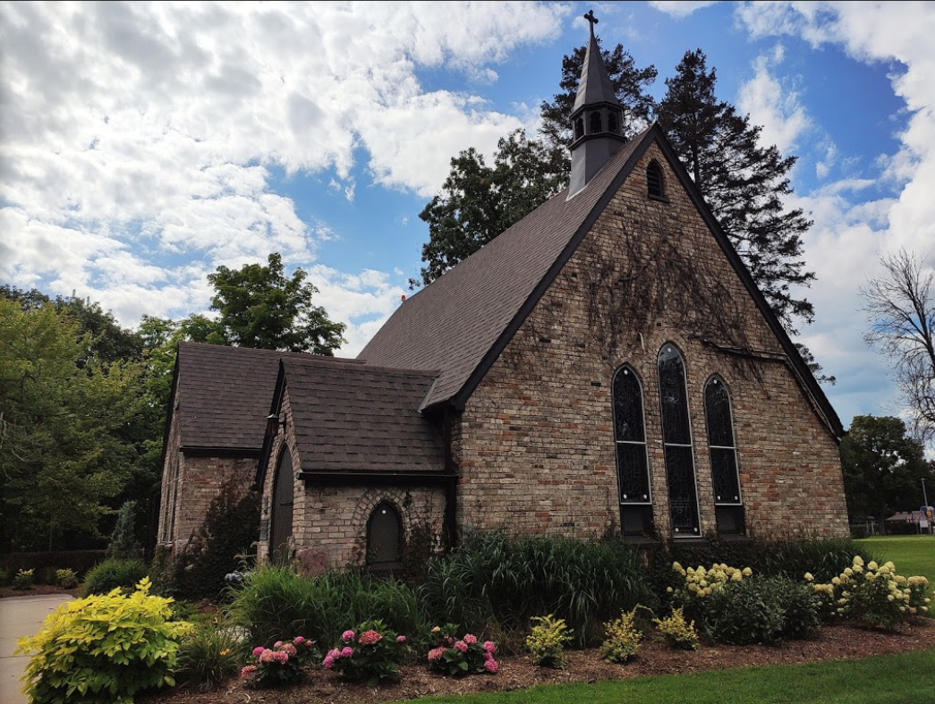 A small brick chapel surrounded by flowers and shrubs. The Sky is blue with clouds.