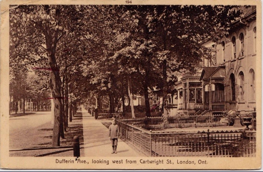 A sepia postcard of a young boy standing on a sidewalk in Woodfield with houses and trees in a row behind him.