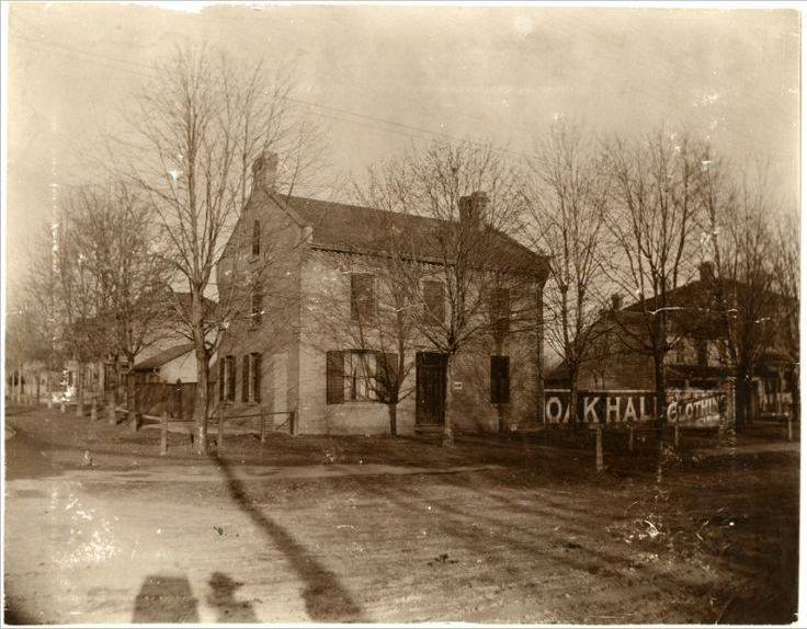 A black and white photo of dirt streets, wooden tavern, and wood sidewalks in Woodfield.