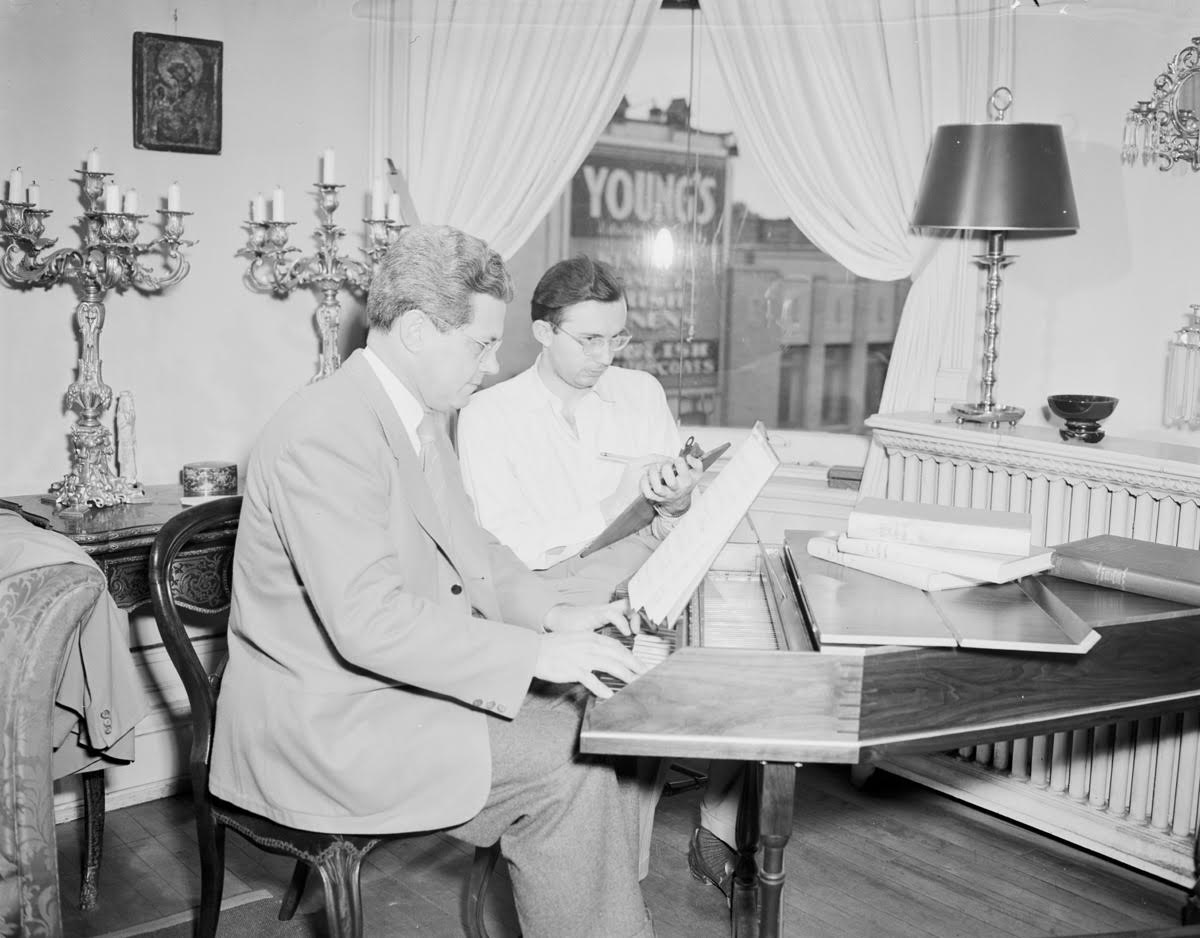 A black and white photo of two men at a piano