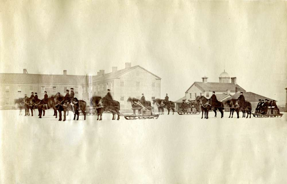 A faded photo of men on horses pulling sleighs with military buildings in the background.