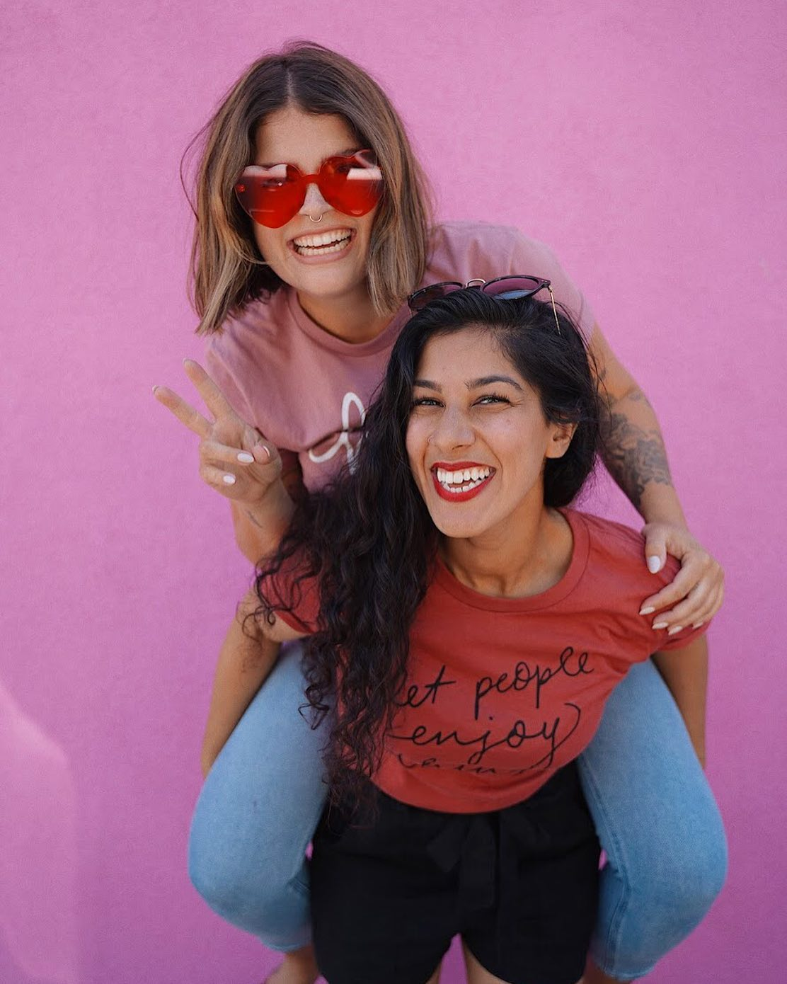 Two women smile in front of a pink wall. One woman in sunglasses is on the back of another woman. Both are wearing Soft Flirt tshirts.