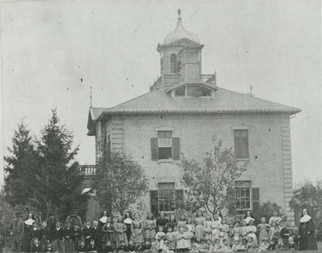A black and white photo of a two story building with children and nuns standing in front of it.