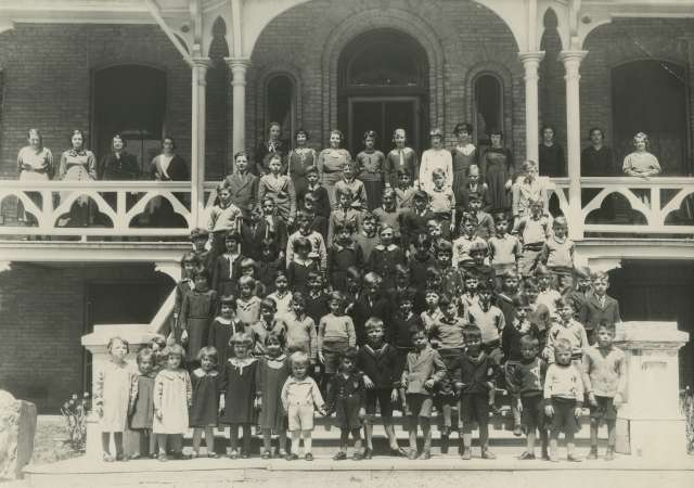 Black and white photo in which children are posing in rows on stairs.