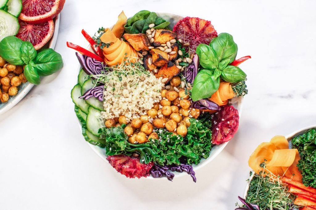 An image of a salad containing chickpeas, quinoa, sweet potato, and a variety of green vegetables.