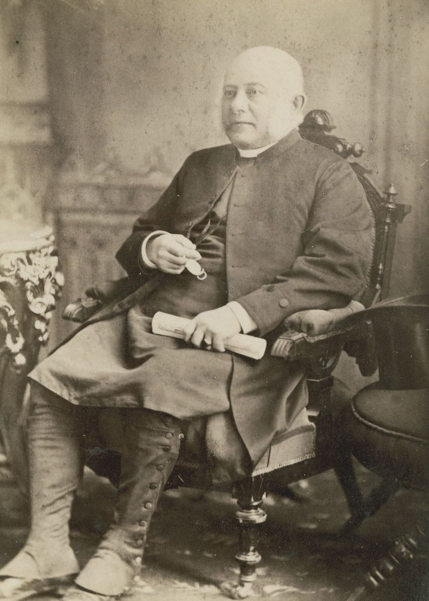 A black and white photo of a man sitting in a chair. He is looking off in the distance, holding a rolled scroll.
