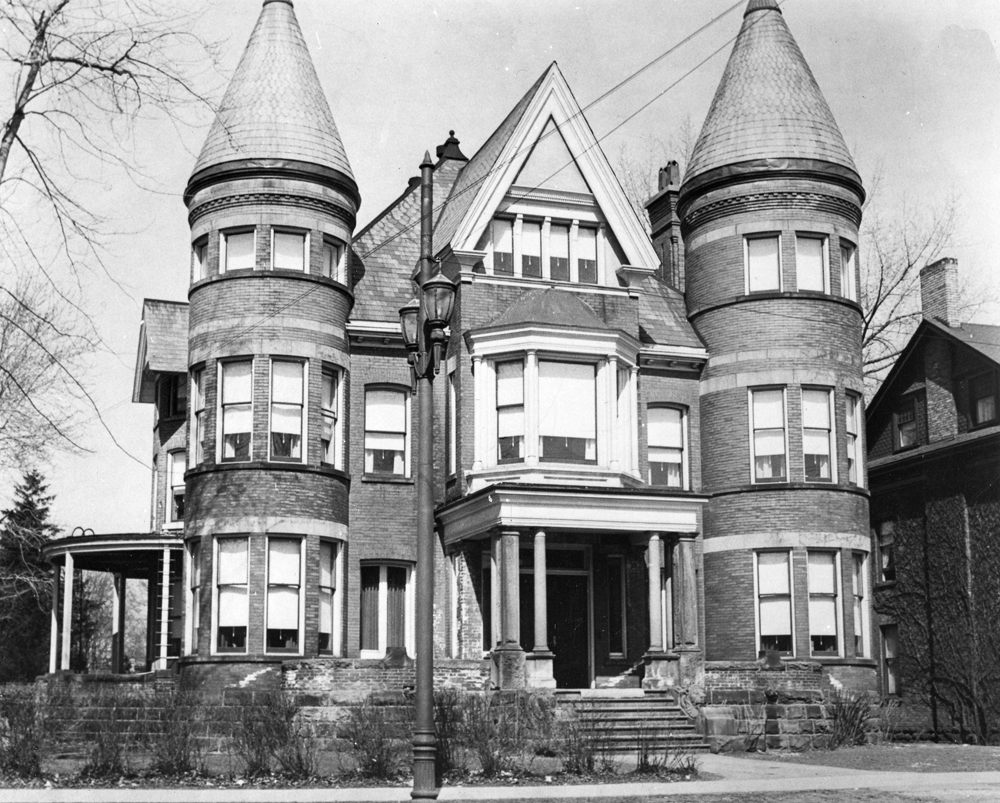 Black and white photograph showing facade of historic Victorian mansion in Midtown.