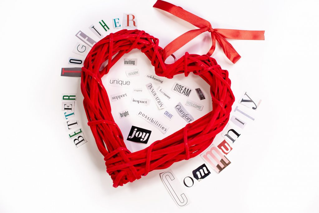 An image of a red wooden heart surrounded by several cut-out words about community.