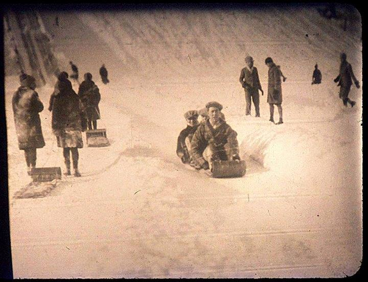 A sepia tinted image of people sitting on a toboggan at the bottom of a hill while others walk up the hill pulling sleds.