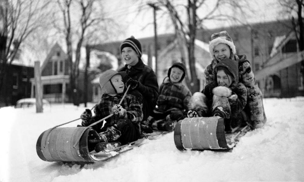 Kids sitting on old wooden toboggans ready to go down a hill in the snow.