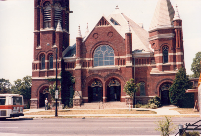 A large red-bricked church in Midtown. The building features two turrets, multiple archways. A bus can be seen driving by in the left hand corner.