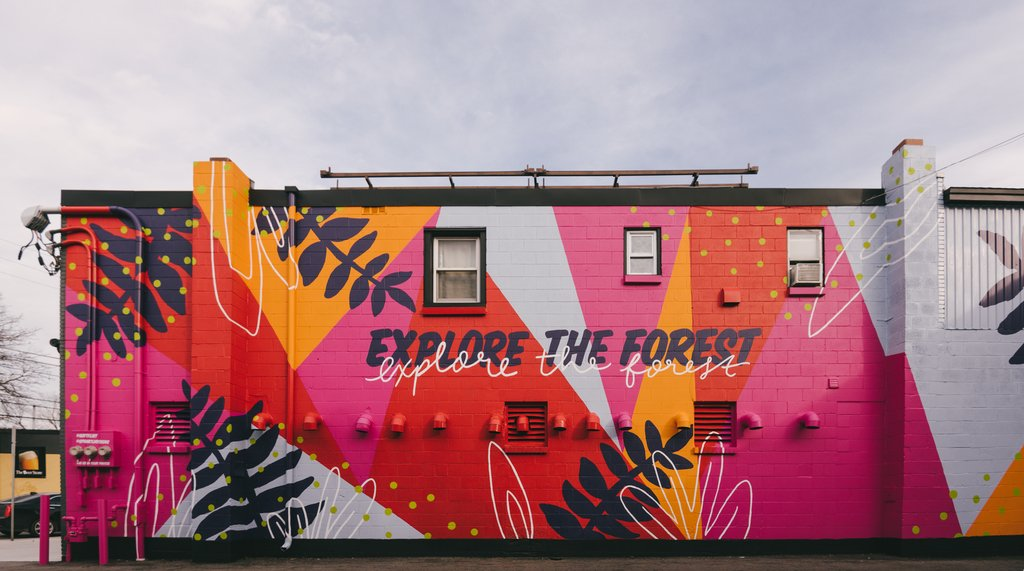 "The side of a building is painted with vivd pinks, reds, and oranges with leaves and says ""Explore the Forest"""