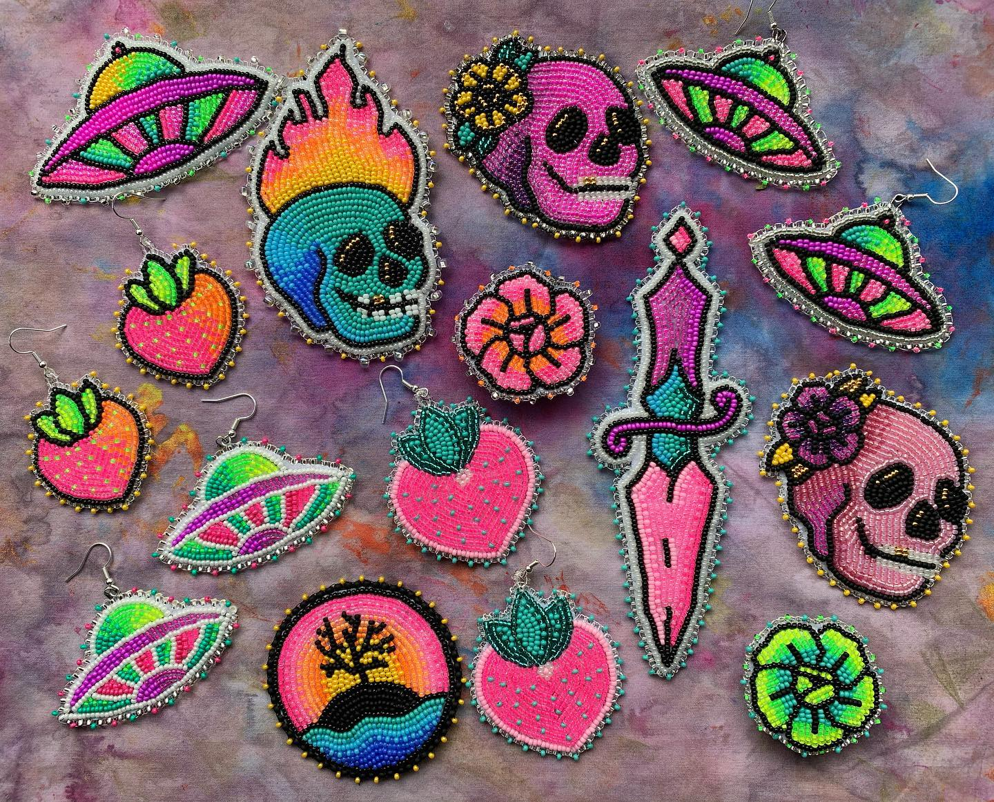 A collection of Flourish and Grow's beaded works including neon UFOs and skulls.