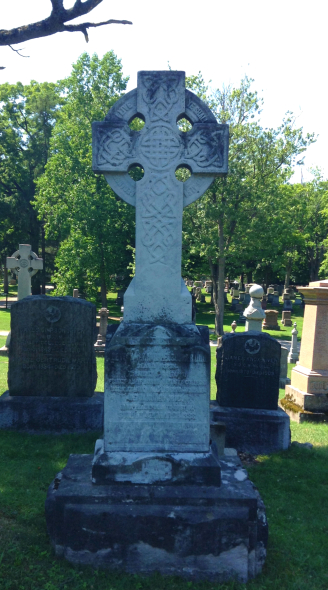 A large gravestone with a cross at the top stands in a shadow. The lettering is illegible.