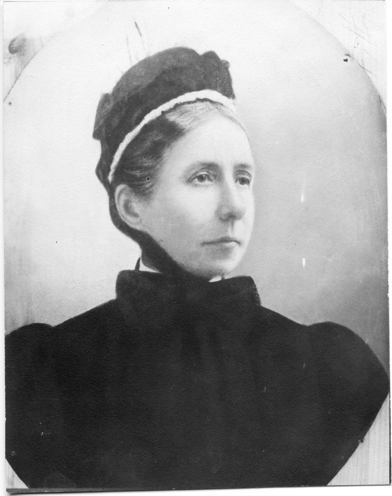 A head and shoulders portrait of Harriet Boomer in a dark dress with her hair primly tucked up under her dark cap trimmed with white lace. The cap is tied under the chin.