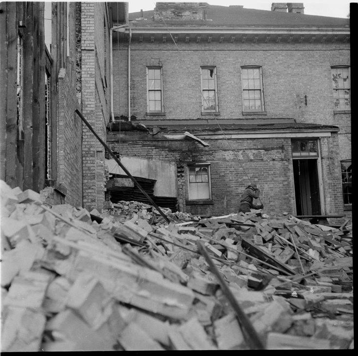 A pile of bricks in the forefront and a partially demolished building behind it.