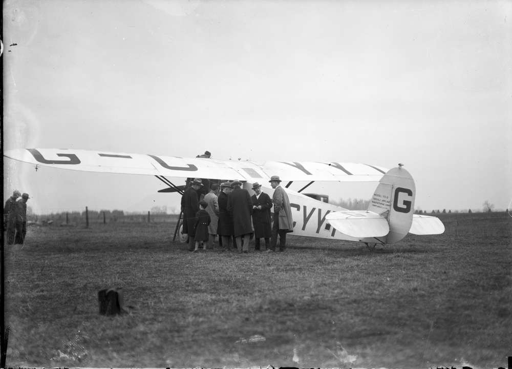 A black and white photo of a small airplane. 8 men in suits and hats stand nearby as does a small child. Location is the London Airport in Lambeth