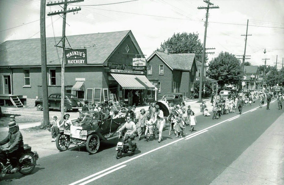 A black and white photo of children walking in costume and people riding motorcycles and bikes in a parade in Lambeth