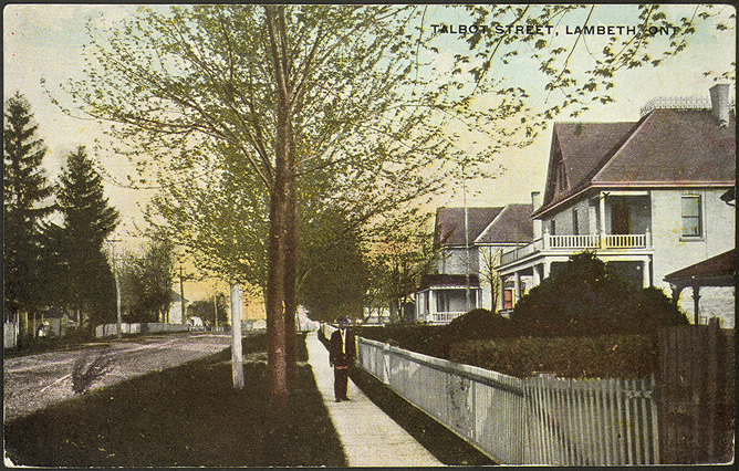 "Postcard of a street with houses lining it. The text reads ""Talbot Street, Lambeth ONT"""