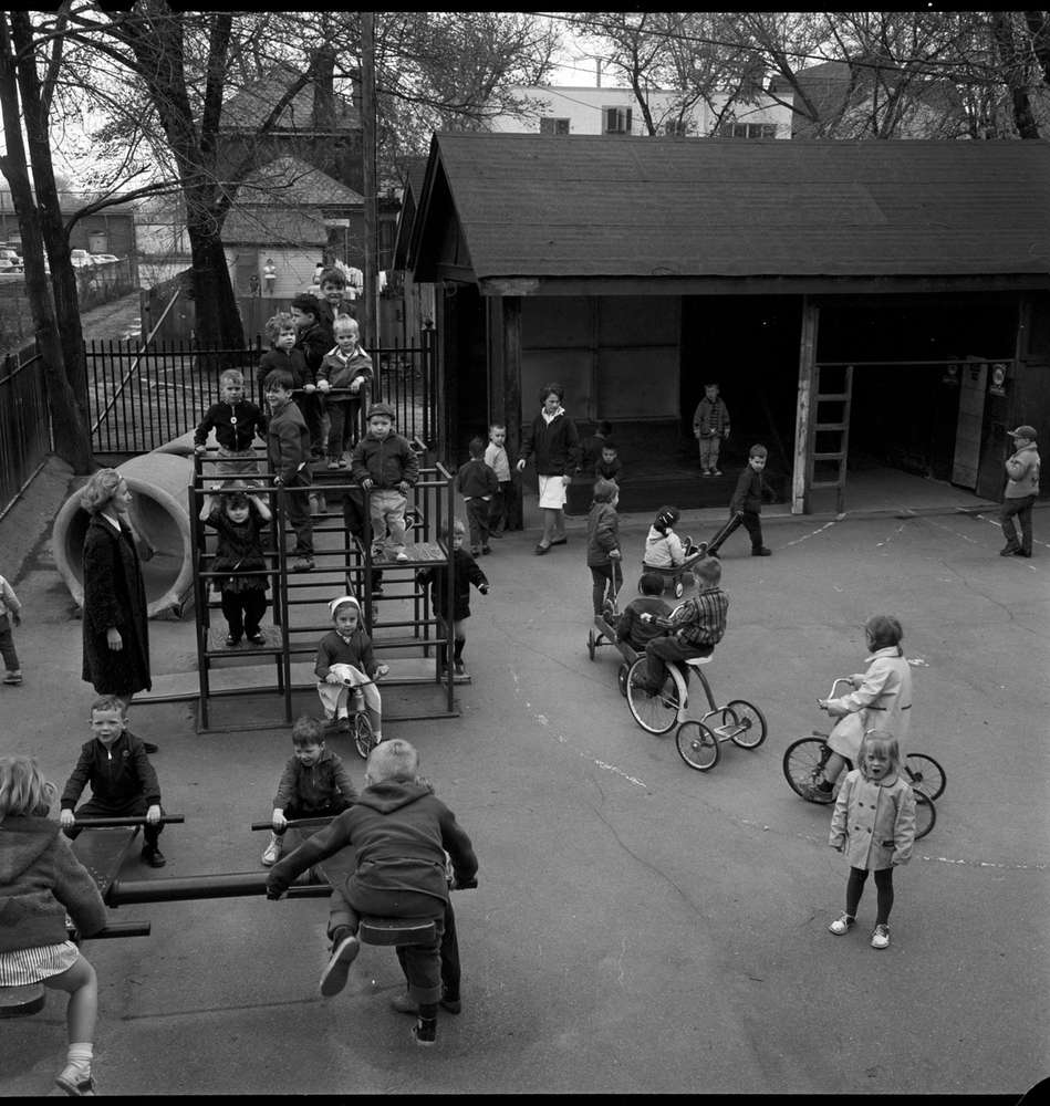 A black and white image of kids playing on a playground. Two women watch over them. Several children ride tricycles in circles.