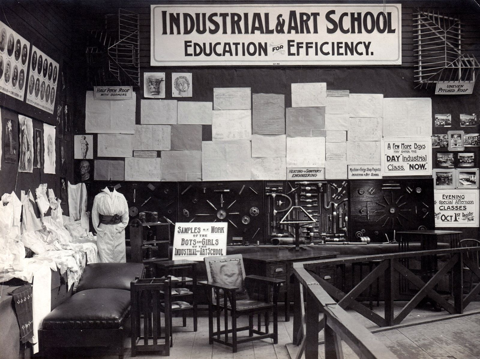 """A black and white photo of a classroom. A banner at the top of the room says """"Industrial and Art School Education For Efficiency."""