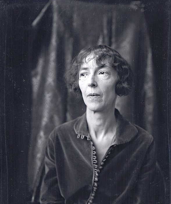 A black and white image of an older woman with short hair looking to her right away from the camera. She is wearing a partially buttoned top and the background is a draped curtain.