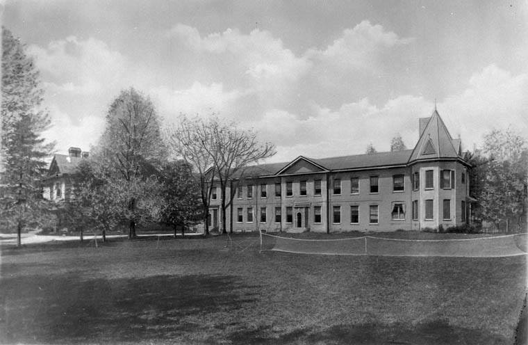 A blck and white photo of a two story institutional-looking building with a field in front of it in Old North.
