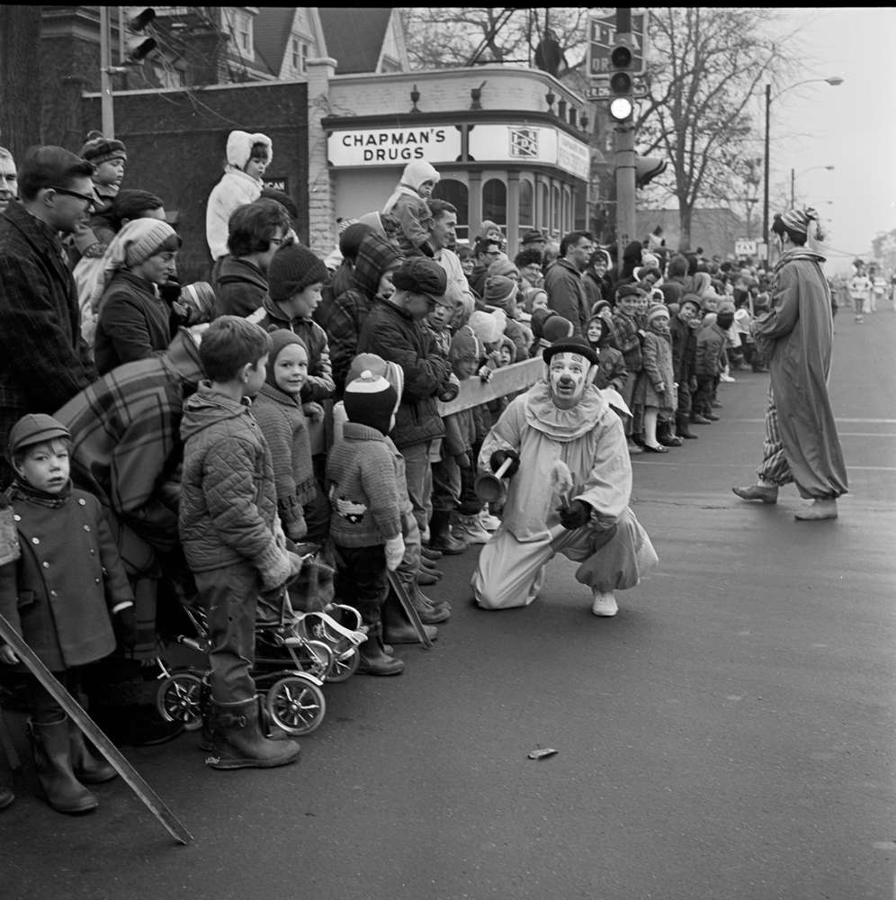 A black and white photo of a clown kneeling in front of children and parents lined up during a parade through Midtown