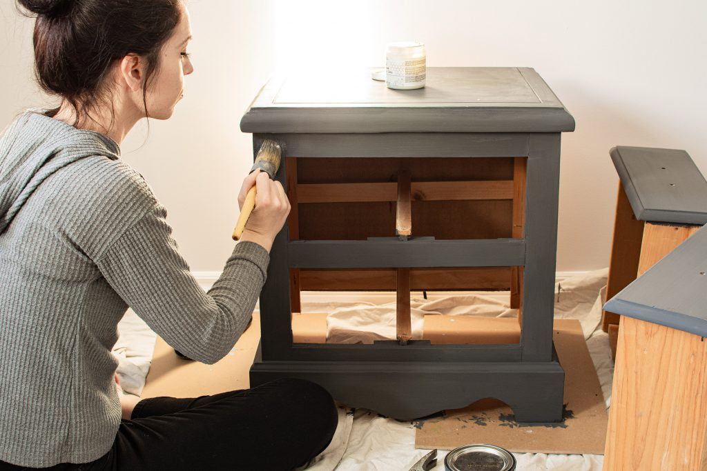 An image of a woman painting a wooden dresser drawer.