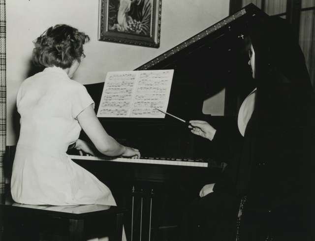A woman sits at a piano. A nun in a habit conducts her.