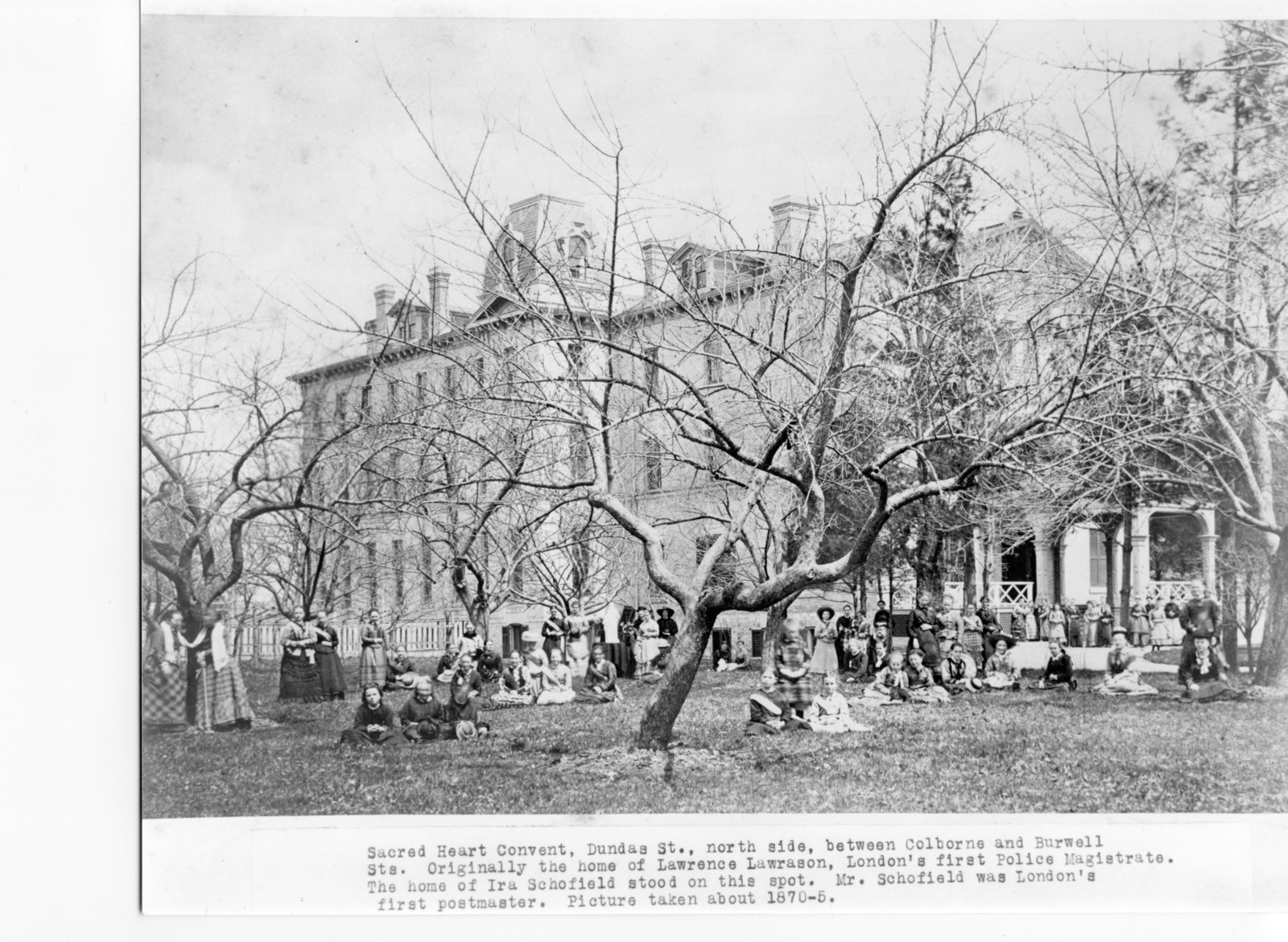 Black and white photograph showing the Sacred Heart Convent with female students and teachers posed amongst the well-treed grounds in Midtown.