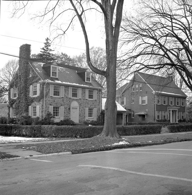 a black and white photo of two large houses in Old North with trees surrounding them and a street in front of them.