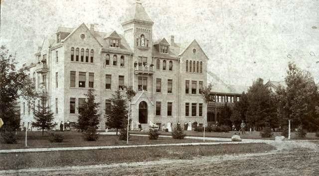 A grainy black and white photo of a Victorian era building used as a hospital.