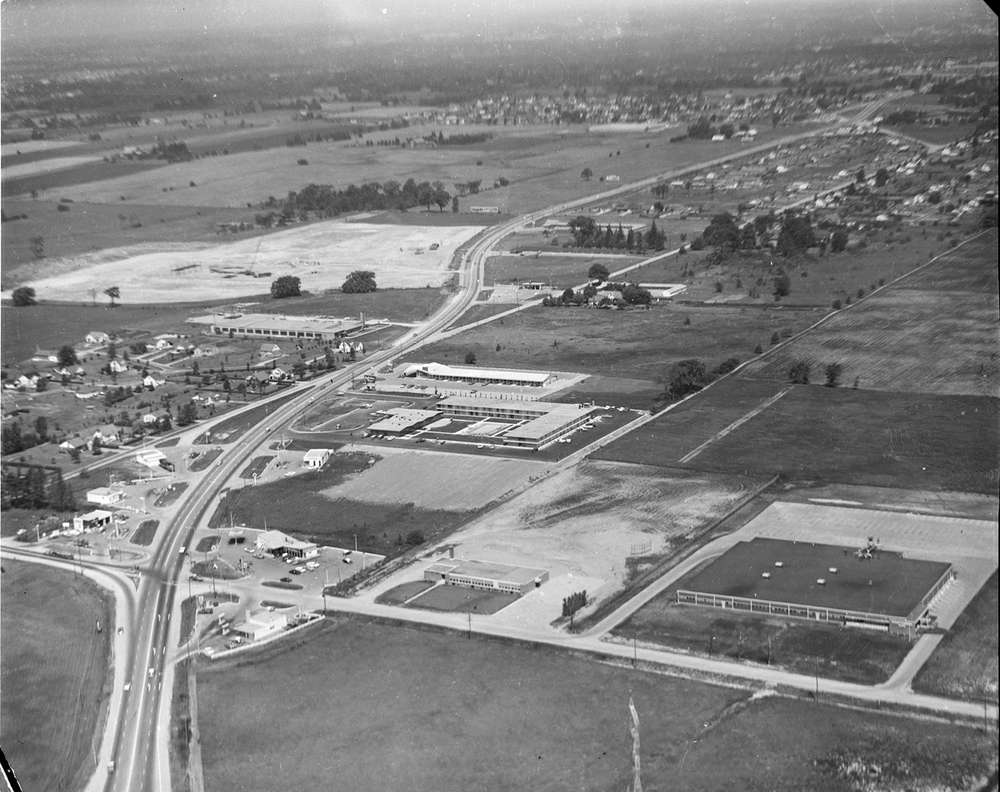 A black and white photo of aerial view of White Oaks with Wellington Road snaking down the middle of the photograph.