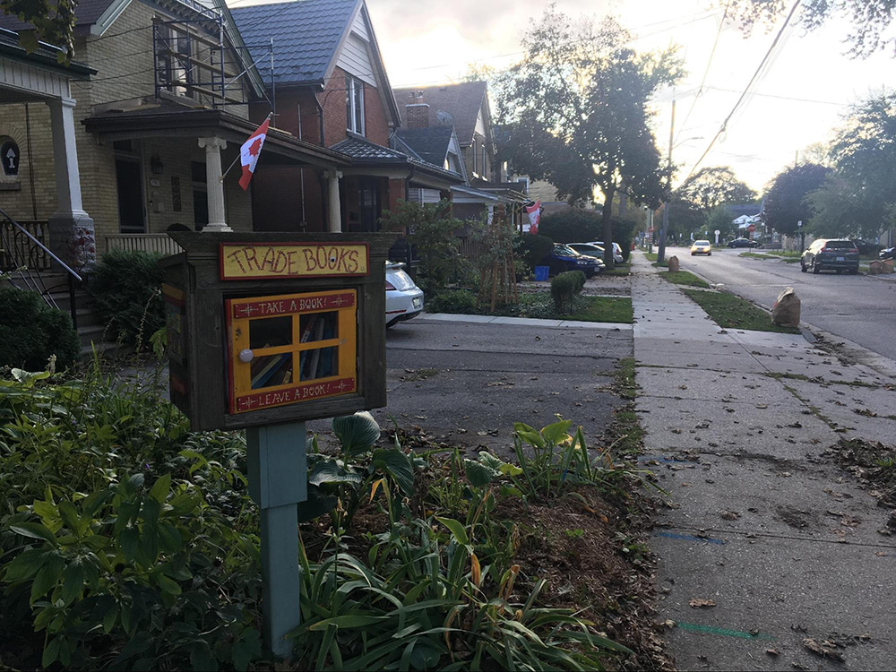 A small structure with a sign that reads Trade Books stands on a grassy lawn on a neighbourhood street.