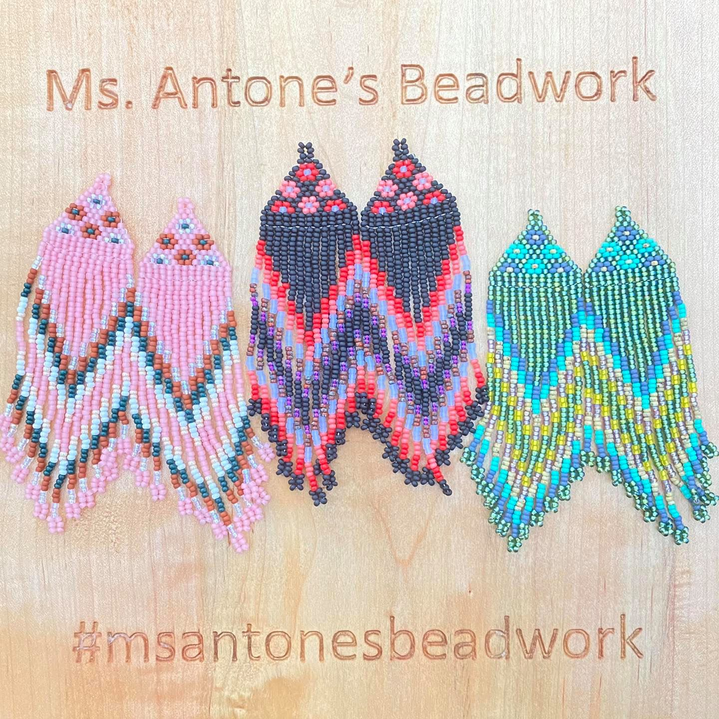 Three pairs of long beaded earrings sit on a wood board enrgaved with Ms. Antone's Beadwork.