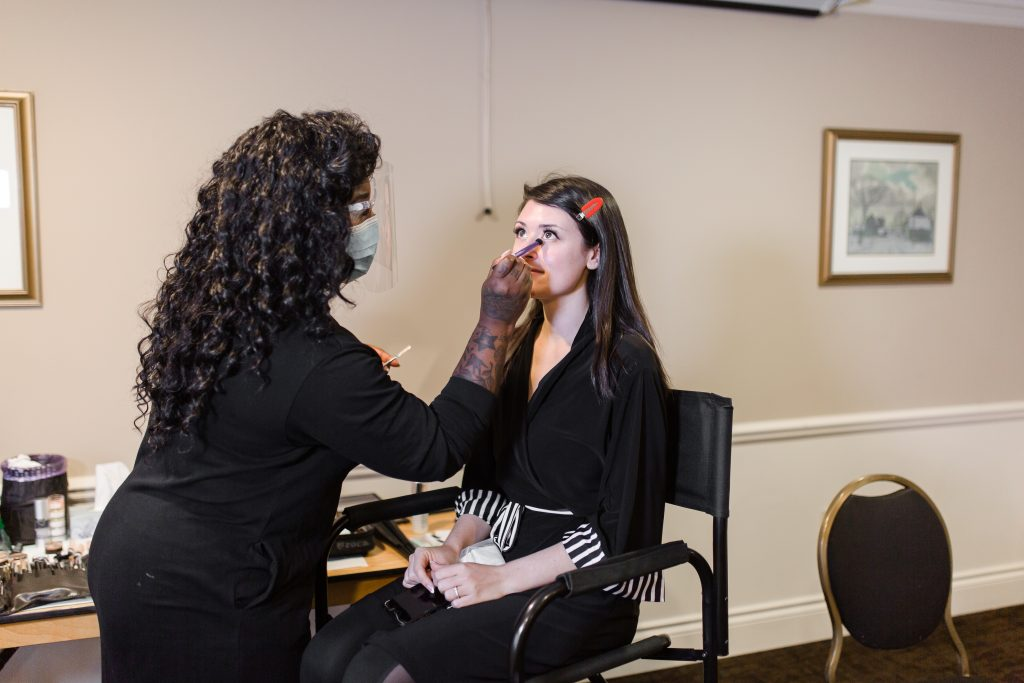 Ty Wilson doing eye makeup on a client